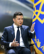 Ukrainian President Volodymyr Zelenskyy gestures while speaking to the media during a news conference with the world's largest airplane, Ukrainian Antonov An-225 Mriya in the background at the Antonov aircraft factory in Kyiv, Ukraine, Thursday, May 20, 2021. (AP Photo/Efrem Lukatsky)