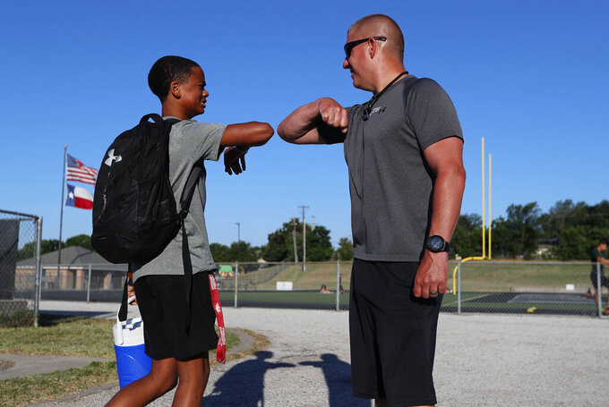 Head football coach Bob Wager, right, and sophomore safety Cameron Conley greet each other at the re-opening of strength and conditioning camp at Arlington Martin High School, Thursday, June 18, 2020, in in Arlington, Texas. While states have been easing the economic and social lockdowns prompted by the coronavirus pandemic, some are now letting high school athletes return for summer workouts before teachers have even figured out how they are going to hold classroom instruction. (AP Photo/LM Otero)
