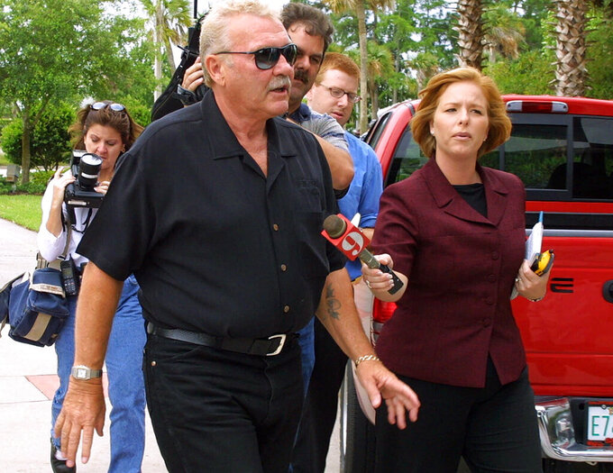 FILE - In this May 3, 2001 file photo founder and chairman of Simpson Racing Products, Bill Simpson, is followed by reporters and photographers as he arrives at NASCAR headquarters in Daytona Beach, Fla. The pioneer in safety for race car drivers has died. Bill Simpson died Monday, Dec. 16, 2019 from complications from a stroke. He was 79. (Nigel Cook/Daytona Beach News-Journal via AP)
