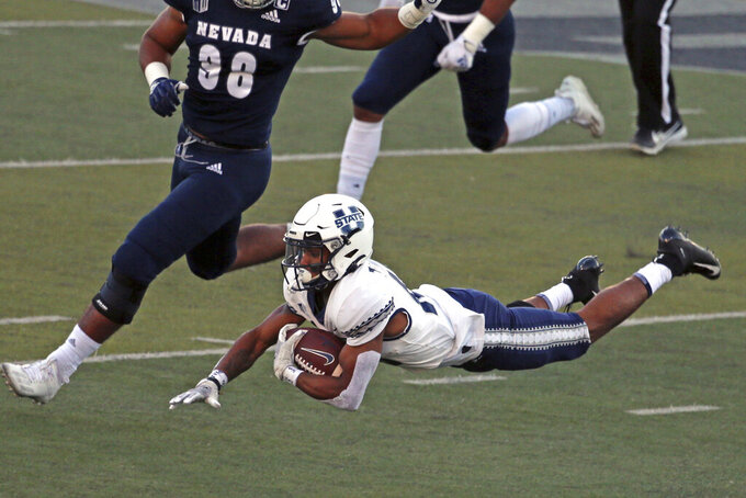 Utah State quarterback Jason Shelley (15) stretches out for more yards after being tripped up during the first half of an NCAA college football game against Nevada on Thursday, Nov. 5, 2020, in Reno, Nev. (AP Photo/Lance Iversen)