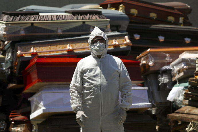 An employee of Xochimilco's crematorium waits for a corpse, suspected to have died of the new coronavirus, in Mexico City, Monday, May 4, 2020. He is standing next to pile of discarded coffins that contained people who died of COVID-19 disease, and are waiting to be destroyed at the site. (AP Photo/Fernando Llano)