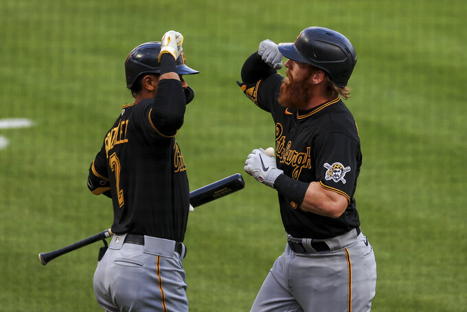 Pittsburgh Pirates' Erik Gonzalez, left, celebrates a solo home run by Colin Moran, right, during the first inning of a baseball game against the Cincinnati Reds in Cincinnati, Monday, April 5, 2021. (AP Photo/Aaron Doster)