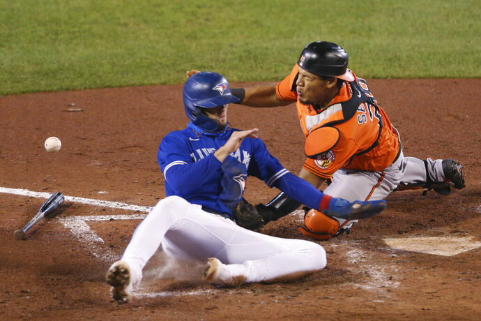 Toronto Blue Jays' Cavan Biggio beats Baltimore Orioles catcher Pedro Severino to the plate on a ball hit by Vladimir Guerrero Jr. during the eighth inning of a baseball game Saturday, Sept. 26, 2020, in Buffalo, N.Y. (AP Photo/Jeffrey T. Barnes)