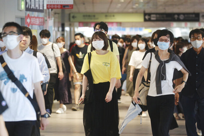 People wearing face masks to protect against the spread of the coronavirus walk at a train station in Tokyo, Wednesday, July 28, 2021. Tokyo Gov. Yuriko Koike on Wednesday urged younger people to cooperate with measures to bring down the high number of infections and get vaccinated, saying their activities are key to slowing the surge during the Olympics. On Tuesday, the Japanese capital reported 2,848 new cases, exceeding its previous record in January. (AP Photo/Koji Sasahara)