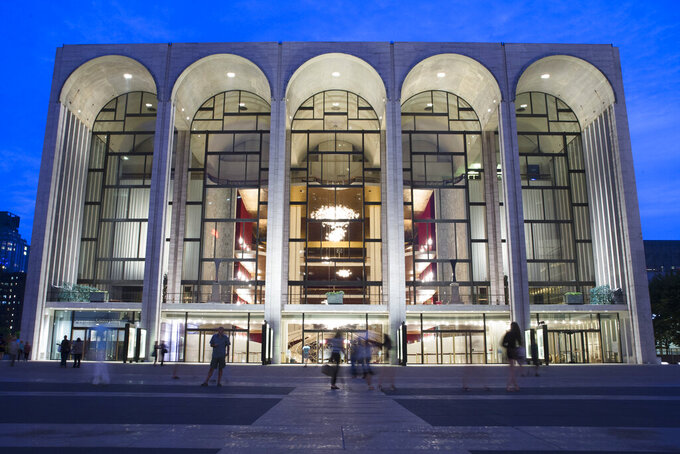 FILE - In this Aug. 1, 2014, file photo, pedestrians make their way in front of the Metropolitan Opera house at New York's Lincoln Center. Met Opera will delay opening night of the season to Dec. 31, calling off four of five new productions, eliminating February break. (AP Photo/John Minchillo, File)