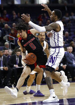 Rutgers guard Geo Baker, left, drives against Northwestern forward Vic Law during the first half of an NCAA college basketball game, Wednesday, Feb. 13, 2019, in Evanston, Ill. (AP Photo/Nam Y. Huh)