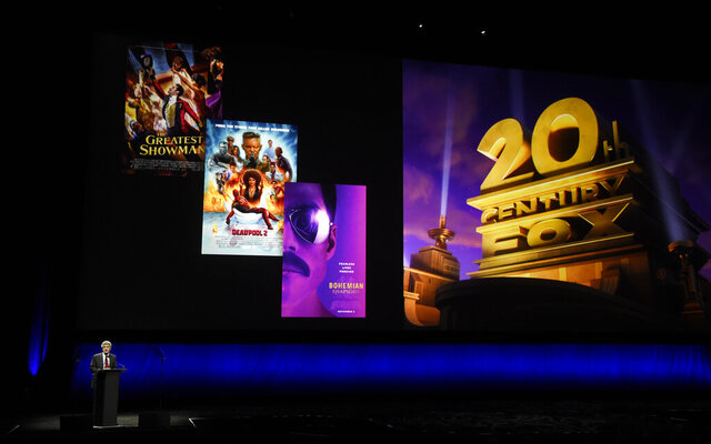 "FILE - In this April 3, 2019, file photo, Alan Horn, chairman of The Walt Disney Studios, speaks underneath poster images for 20th Century Fox films during the Walt Disney Studios Motion Pictures presentation at CinemaCon 2019, the official convention of the National Association of Theatre Owners (NATO) at Caesars Palace in Las Vegas. Disney is dropping the word ""Fox"" from the movie studios it acquired as part of last year's $71 billion purchase of Fox's entertainment business, according to published reports. According to trade publication Variety, 20th Century Fox will become 20th Century Studios, while Fox Searchlight Pictures will be Searchlight Pictures. Disney will still run them as separate studios within the company. (Photo by Chris Pizzello/Invision/AP, File)"
