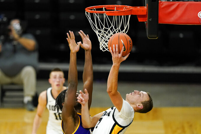 Iowa forward Jack Nunge, right, drives to the basket in front of Western Illinois forward Tamell Pearson, left, during the first half of an NCAA college basketball game, Thursday, Dec. 3, 2020, in Iowa City, Iowa. (AP Photo/Charlie Neibergall)