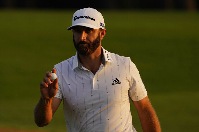 Dustin Johnson holds up his ball on the 18th green after his third round of the Masters golf tournament Saturday, Nov. 14, 2020, in Augusta, Ga. (AP Photo/Chris Carlson)