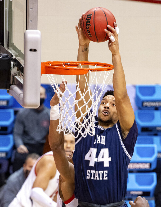 Utah State guard Marco Anthony (44) scores with a slam dunk during the first half of a first round game against Texas Tech in the NCAA men's college basketball tournament, Friday, March 19, 2021, in Bloomington, Ind. (AP Photo/Doug McSchooler)