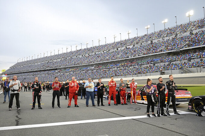 Drivers and team members stand on pit road during the national anthem before a NASCAR Xfinity Series auto race at Daytona International Speedway, Friday, Aug. 27, 2021, in Daytona Beach, Fla. (AP Photo/Phelan M. Ebenhack)