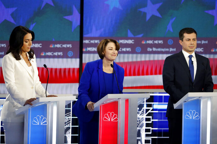 Democratic presidential candidates Rep. Tulsi Gabbard, D-Hawaii, Sen. Amy Klobuchar, D-Minn., and South Bend, Ind., Mayor Pete Buttigieg, from left, participate in a Democratic presidential primary debate, Wednesday, Nov. 20, 2019, in Atlanta. (AP Photo/John Bazemore)