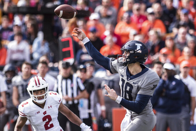 Illinois quarterback Brandon Peters (18) passes downfield as Wisconsin's Reggie Pearson (2) defends in the second half of an NCAA college football game, Saturday, Oct. 19, 2019, in Champaign, Ill. (AP Photo/Holly Hart)