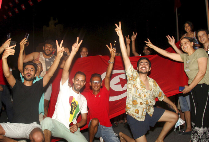 FILE - In this July 25, 2021 file photo, demonstrators celebrate with a Tunisian national flag during a rally after the president suspended the legislature and fired the prime minister in Tunis, Tunisia. Days of political turmoil in Tunisia over the economy and the coronavirus have left its allies in the Middle East, Europe and the United States watching to see if the fragile democracy will survive. (AP Photo/Hedi Azouz, File)