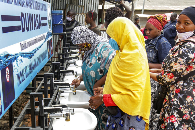 """FILE - In this Monday, May 18, 2020 file photo, people use a hand-washing station installed for members of the public entering a market in Dodoma, Tanzania. Tanzania's COVID-denying president Magufuli on Friday Feb. 19, 2021, is calling on citizens for three days of prayer to defeat unnamed """"respiratory diseases"""" amid warnings that the country is seeing a deadly resurgence in infections. (AP Photo, File)"""