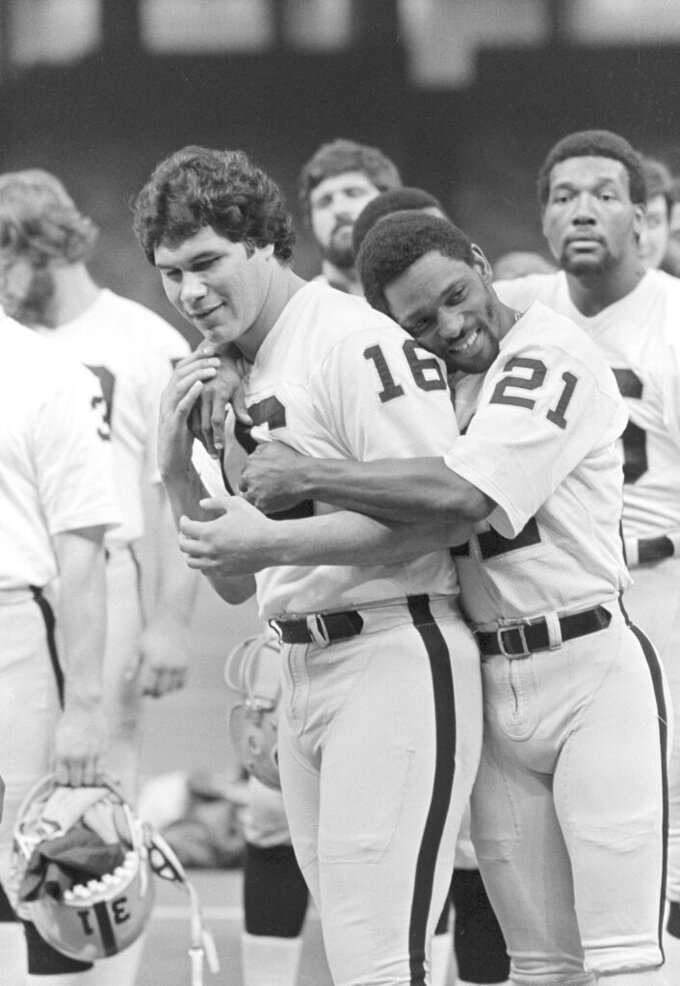 FILE - In this Jan. 21, 1981, file photo Oakland Raiders wide receiver Cliff Branch (21) hugs quarterback Jim Plunkett (16) as the Raiders lined up for a team picture before a workout in the Superdome in New Orleans. Branch, one of the Raiders' career-leading receivers who won three Super Bowls, has died. He was 71. (AP Photo/Paul Sakuma, File)