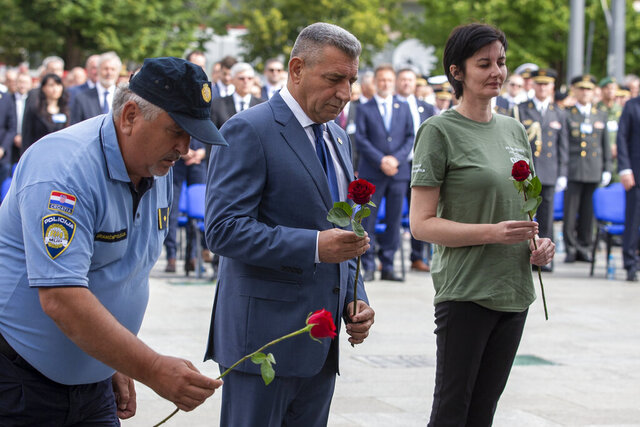 Croatian Gen. Ret. Ante Gotovina places flowers during a ceremony in Knin, Croatia, Wednesday, Aug. 5, 2020. Croatia marked the 25th anniversary of a victorious wartime military offensive, with an ethnic Serb politician attending the ceremony for the first time in what is seen as an important step toward reconciliation. (AP Photo/Darko Bandic)