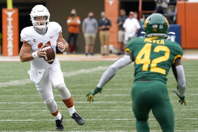 Texas' Sam Ehlinger (11) scrambles against Baylor's Jairon McVea (42) during the first half of an NCAA college football game in Austin, Texas, Saturday, Oct. 24, 2020. (AP Photo/Chuck Burton)
