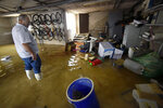 A man inspects his garage following a rainfall in El Raal, near Murcia, Spain, Saturday, Sept. 14, 2019. Authorities say that record rainfall in southeastern Spain have claimed the lives of two more victims, taking the death toll to six from the storms that have flooded roads and towns. A sixth victim was confirmed by authorities on Saturday, a 41-year-old man in the town of Orihuela, where the river Segura overflowed its banks on Friday. (AP Photo/Alfonso Duran)