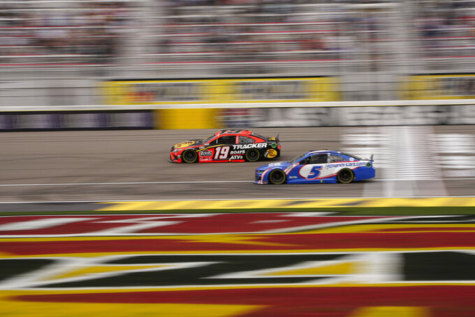 Martin Truex Jr. (19) and Kyle Larson (5) drive during a NASCAR Cup Series auto race Sunday, March 7, 2021, in Las Vegas. (AP Photo/John Locher)