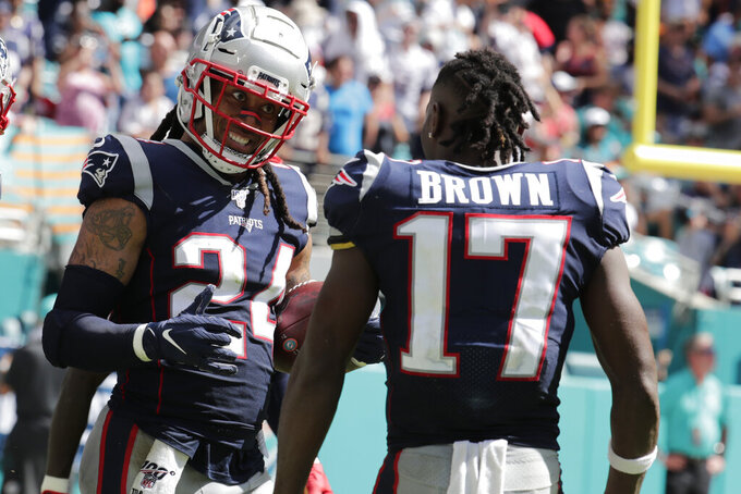 New England Patriots wide receiver Antonio Brown (17) congratulates cornerback Stephon Gilmore (24), after Gilmore scored a touchdown, during the second half at an NFL football game, Sunday, Sept. 15, 2019, in Miami Gardens, Fla. (AP Photo/Lynne Sladky)