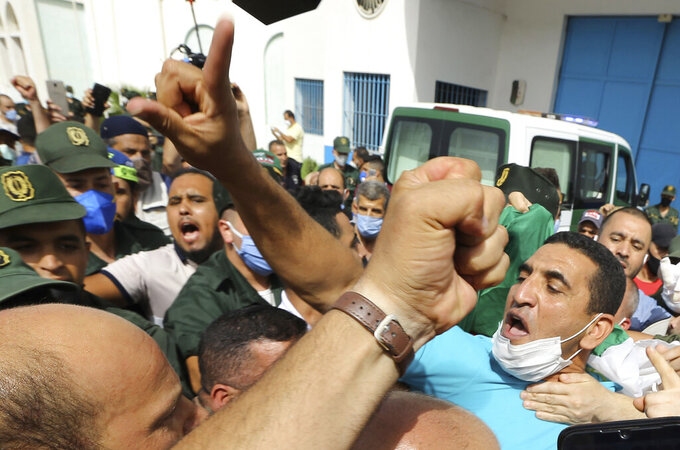 FILE - In this July 2, 2020 file photo, activist Karim Tabbou flashes a victory sign as he is greeted by supporters as he is released from the prison of Kolea, west of Algiers. A politician and a journalist who are prominent opposition figures in Algeria have been arrested days ahead of the country's parliamentary election, according to a group of lawyers defending jailed activists of the pro-democracy movement. The National Committee for the Liberation of the Detained said politician Karim Tabbou was arrested Thursday night at his home in the southwestern suburbs of Algiers. (AP Photo/Anis Belghoul, FILE)