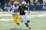 Missouri running back Tyler Badie (1) runs with the ball as LSU linebacker Damone Clark (18) defends during the second half of an NCAA college football game Saturday, Oct. 10, 2020, in Columbia, Mo. Missouri upset LSU 45-41. (AP Photo/L.G. Patterson)