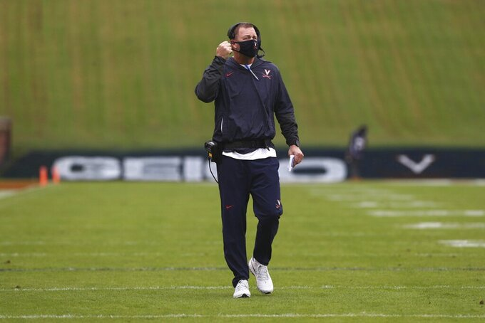Virginia head coach Bronco Mendenhall adjusts his mask during an NCAA college football game against North Carolina State Saturday, Oct. 10, 2020, at Scott Stadium in Charlottesville, Va. (Erin Edgerton/The Daily Progress via AP)