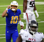 Quarterback Justin Herbert #10 of the Los Angeles Chargers reacts after throwing a touchdown against the Atlanta Falcons in the first half of a NFL football game at SoFi Stadium in Inglewood on Sunday, December 13, 2020. (Keith Birmingham/The Orange County Register via AP)