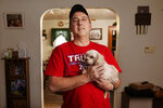 Jeff Butcher poses with Drizzly, the family dog, in his home in Celina, Ohio, Dec. 17, 2020. Butcher considered himself a non-political centrist before he came to admire Trump, who would