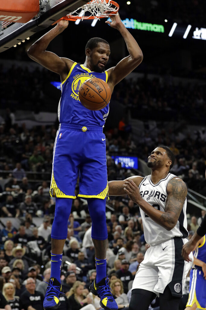 FILE - In this April 19, 2018, file photo, Golden State Warriors forward Kevin Durant dunks as San Antonio Spurs' Rudy Gay (22) watches during the the first half of Game 3 of a first-round NBA basketball playoff series in San Antonio.  Just three seasons ago, the Brooklyn Nets were the worst team in the NBA. On Sunday, June 30, 2019, they were the story of the league. They agreed to deals with superstars Kevin Durant and Kyrie Irving as part of a sensational start to free agency, giving the longtime No. 2 team in New York top billing in the Big Apple. (AP Photo/Tony Gutierrez, File)