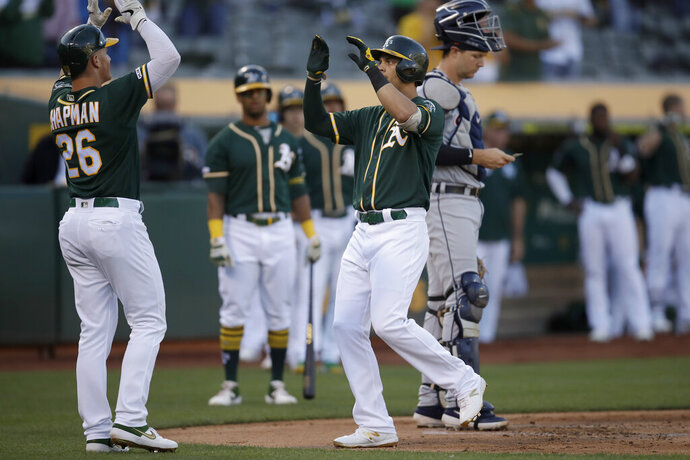 Oakland Athletics' Chad Pinder, right, celebrates with Matt Chapman (26) after hitting a two-run home run off Detroit Tigers' David McKay in the ninth inning of a baseball game that was suspended due to rain earlier in the season, Friday, Sept. 6, 2019, in Oakland, Calif. (AP Photo/Ben Margot)