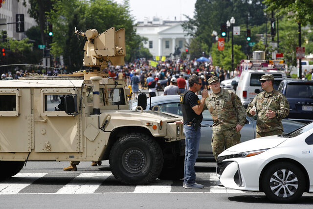 A checkpoint blocks traffic on 16th Street Northwest as people gather near the White House, Saturday, June 6, 2020, in Washington, before scheduled protests over the death of George Floyd, who died after being restrained by Minneapolis police officers. (AP Photo/Patrick Semansky)