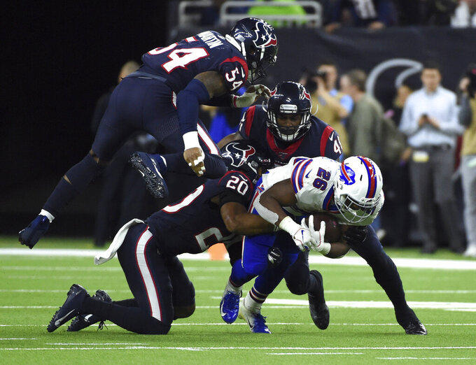 Buffalo Bills running back Devin Singletary (26) is tackled by Houston Texans' Justin Reid (20), Jake Martin (54) and Zach Cunningham (41) during the second half of an NFL wild-card playoff football game Saturday, Jan. 4, 2020, in Houston. (AP Photo/Eric Christian Smith)