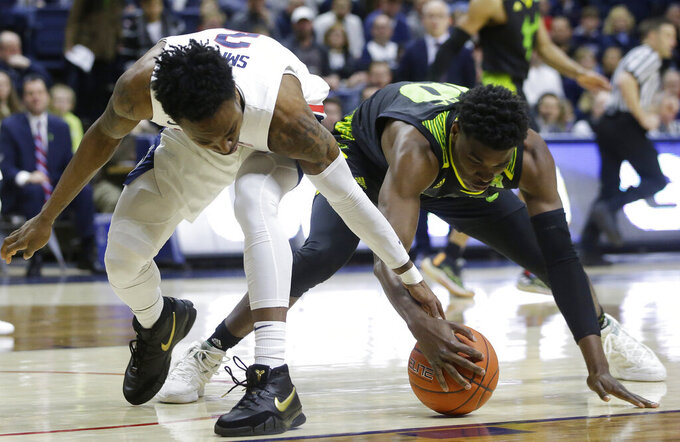 Connecticut's Tarin Smith, left, and South Florida's Alexis Yetna, right, vie for a loose ball during the first half of an NCAA college basketball game, Sunday, March 3, 2019, in Storrs, Conn. (AP Photo/Steven Senne)