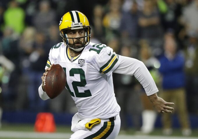 FILE - In this Nov. 15, 2018, file photo, Green Bay Packers quarterback Aaron Rodgers looks to pass against the Seattle Seahawks during the first half of an NFL football game, in Seattle. The Packers play the Minnesota Vikings on Sunday. The NFL's six highest-paid quarterbacks in 2018 will be spectators this postseason. Green Bay's Aaron Rodgers ($33.5 million), Atlanta's Matt Ryan ($30 million), Minnesota's Kirk Cousins ($28 million), San Francisco's Jimmy Garoppolo ($27.5 million), Detroit's Matthew Stafford ($27 million) and Oakland's Derek Carr ($25 million) couldn't lead their teams to the playoffs. (AP Photo/Elaine Thompson, File)