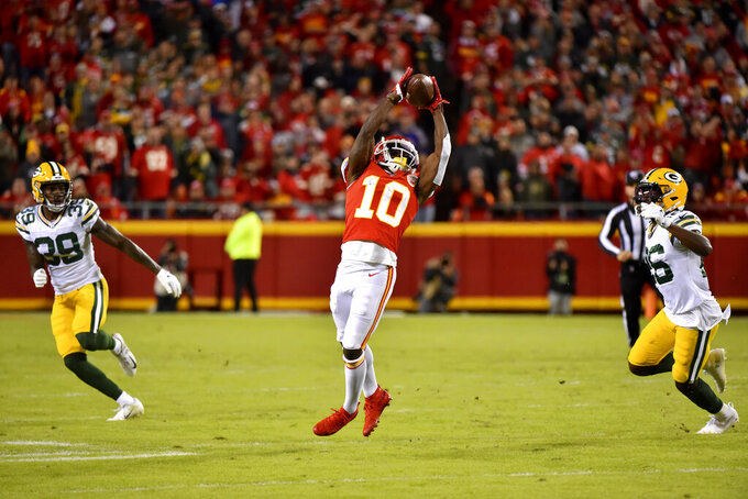 Kansas City Chiefs wide receiver Tyreek Hill (10) makes a catch between Green Bay Packers cornerback Chandon Sullivan (39) and safety Darnell Savage (26) during the first half of an NFL football game in Kansas City, Mo., Sunday, Oct. 27, 2019. (AP Photo/Ed Zurga)
