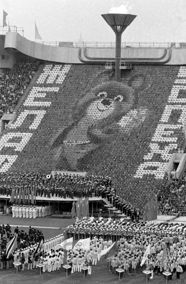 FILE - In this July 19, 1980, file photo, a giant image of Misha, the Russian bear mascot of the 1980 Moscow Summer Olympic Games, greets athletes standing on the field of Moscow's Lenin Stadium during opening ceremonies of the competitions in Moscow. The image was created by 3,500 card-bearers. Overhead burns the Olympic flame. (AP Photo/File)