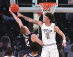 Georgia Tech guard Jordan Usher blocks a shot by Virginia forward Sam Hauser during an NCAA college basketball game Wednesday, Feb 10, 2021, in Atlanta. (Curtis Compton/Atlanta Journal-Constitution via AP)