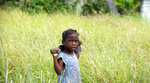 In this May 27, 2019 photo, a girl with a machete eyes the camera as she walks in a field of vetiver in Les Cayes, Haiti. Haiti produces more than 70 tons of vetiver oil a year, surpassing Indonesia, China, India, Brazil and the neighboring Dominican Republic. (AP Photo/Dieu Nalio Chery)