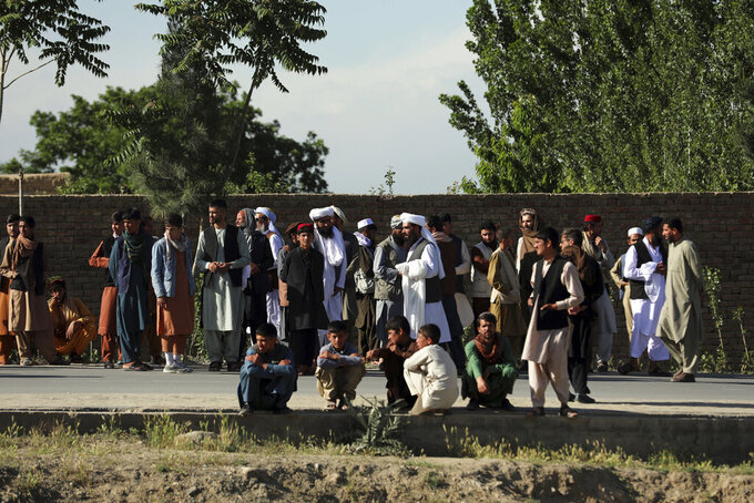 Afghans stand near to mosque after a bomb explosion in Shakar Dara district of Kabul, Afghanistan, Friday, May 14, 2021. A bomb ripped through a mosque in northern Kabul during Friday prayers killing 12 worshippers, Afghan police said. (AP Photo/Rahmat Gul)