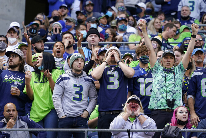 Fans, most not adhering to a mask requirement at Lumen Field, cheer during the first half of an NFL football game between the Seattle Seahawks and the Tennessee Titans, Sunday, Sept. 19, 2021, in Seattle. (AP Photo/Elaine Thompson)