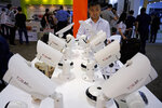 In this April 11, 2018, photo, a man looks at security cameras at the Global Sources trade fair, a trade fair where Chinese manufacturers meet western buyers in Hong Kong. Chinese exporters of goods from electronics to motorcycle parts are scrambling to insulate themselves from U.S. President Donald Trump's proposed tariff hike. (AP Photo/Vincent Yu)