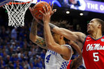 Kentucky's Nick Richards (4) pulls down a rebound while pressured Mississippi's KJ Buffen (5) in the second half of an NCAA college basketball game in Lexington, Ky., Saturday, Feb. 15, 2020. Kentucky won 67-62. (AP Photo/James Crisp)