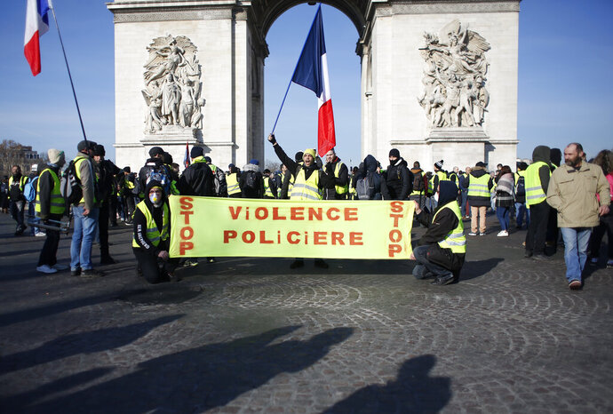 Yellow vest protesters gather at the Arc de Triomphe with a banner reading