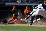 Baltimore Orioles' Cedric Mullins scores a run past New York Yankees catcher Kyle Higashioka during the seventh inning of a baseball game on Saturday, Sept. 4, 2021, in New York. (AP Photo/Adam Hunger)