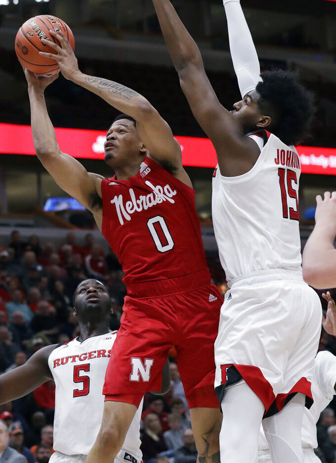 Nebraska guard James Palmer Jr. (0) drives to the basket against Rutgers forward Eugene Omoruyi, left, and center Myles Johnson during the first half of an NCAA college basketball game in the first round of the Big Ten Conference tournament in Chicago, Wednesday, March 13, 2019. (AP Photo/Nam Y. Huh)