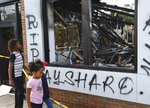 Children take in the burned Wendy's location in Atlanta on Monday, June 15, 2020, outside which Rayshard Brooks, a 27-year-old black man, was fatally shot by a white Atlanta police officer Friday night. (Curtis Compton/Atlanta Journal-Constitution via AP)