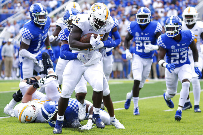 Chattanooga running back Ailym Ford (32) tries to break free from a tackle during the second half of a NCAA college football game against Kentucky in Lexington, Ky., Saturday, Sept. 18, 2021. (AP Photo/Michael Clubb)