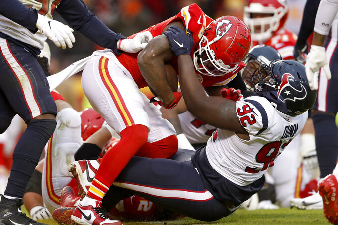 Kansas City Chiefs running back Damien Williams (26) scores a touchdown against Houston Texans nose tackle Brandon Dunn (92) during the second half of an NFL divisional playoff football game, in Kansas City, Mo., Sunday, Jan. 12, 2020. (AP Photo/Jeff Roberson)